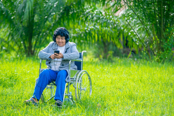 The elderly on wheelchairs are enjoying music with smartphone.