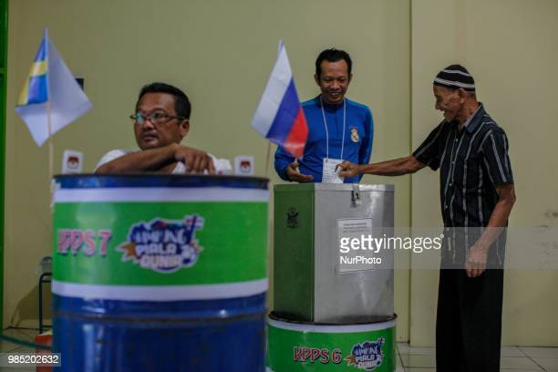 The election committees wear the costumes of participating countries of the World Cup 2018 during regional election in Surakarta Central Java...