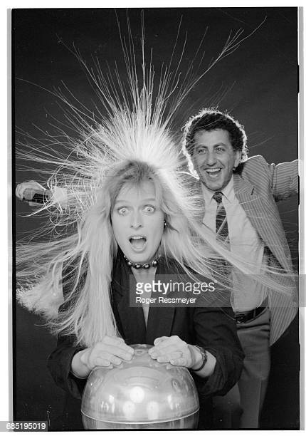 The electric charge from a Van de Graaff generator makes Christe Lawson's hair stand on end Maurice Cohen who uses the Van de Graaff generator at his...