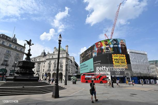 The electronic billboard in Piccadilly Circus displays a notice telling people to Stay Home Protect the NHS Save Lives beyond an empty Shaftesbury...