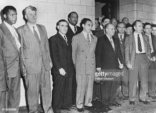 The eleven leaders of the American Communist Party leave the court house in handcuffs after being found guilty of conspiring to teach the overthrow...