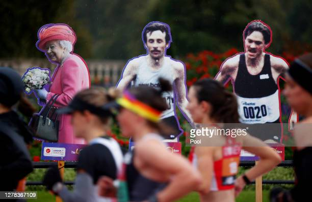 The Elite Women's Field competes as they run past cardboard cutouts featuring Queen Elizabeth II during the 2020 Virgin Money London Marathon around...