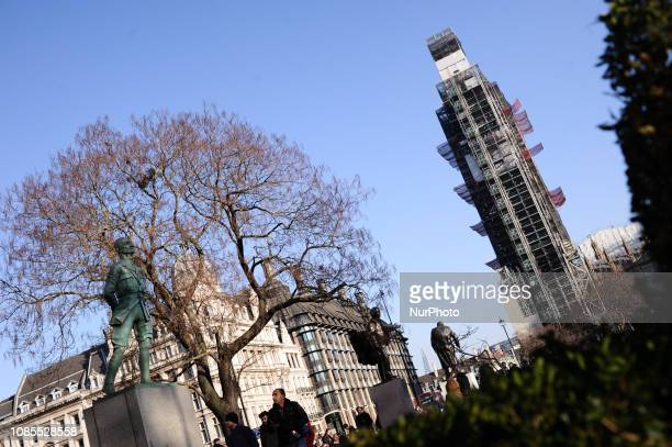 The Elizabeth Tower commonly known as Big Ben stands covered in scaffolding for renovation works as people walk past statues in Parliament Square in...