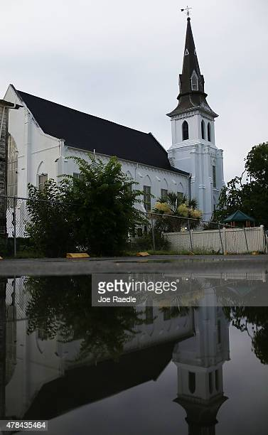 The Emanuel African Methodist Episcopal Church is reflected in water as victims of a mass shooting at the church which killed nine people are being...
