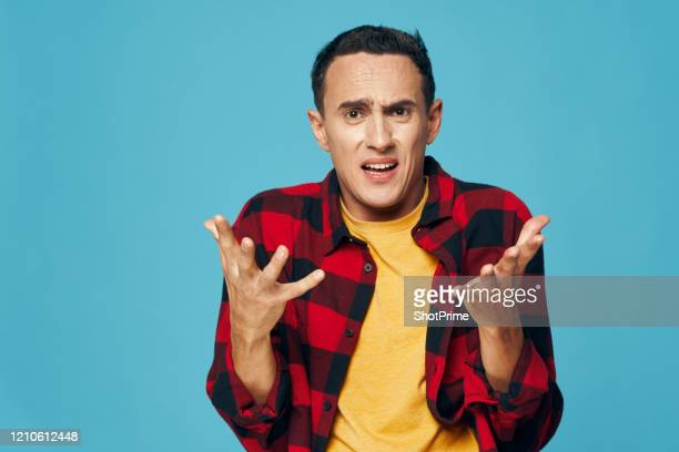 the embarrassed, confused young man threw up his hands and gestures that he is surprised and does not know what to do, blue background, red checkered shirt - crisi foto e immagini stock