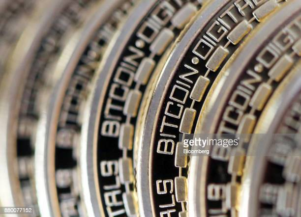 The embossed word 'Bitcoin' sits on the edge of Bitcoins stacked in this arranged photograph in Danbury UK on Thursday Dec 10 2015 Bitcoin is showing...