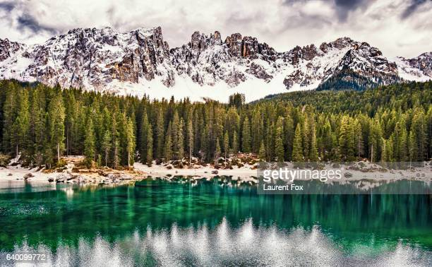 The emerald green Lake Carezza reflects the trees in the western Dolomite mountains of northern Italy.