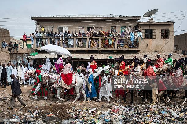 TOPSHOT The Emir of Kano Muhammadu Sanusi II rides a horse as he parades with his entourage and musicians on the streets of Kano northern Nigeria on...