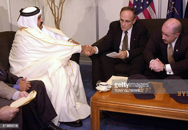 The emir of Qatar, Sheik Hamad bin Khalifa Al Thani shakes hands with New York City Mayor Rudolph Giuliani as New York Police Commissioner Bernard...