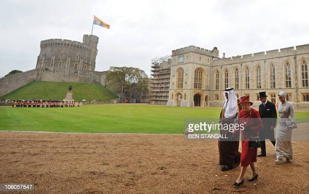 The Emir of Qatar, Sheikh Hamad bin Khalifa al-Thani, and his wife Sheikha Mozah walk with Britain's Queen Elizabeth II , and her husband Prince...