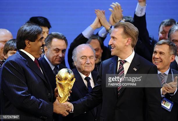 The Emir of Qatar Sheikh Hamad bin Khalifa alThani and Russia's Deputy Prime Minister Igor Shuvalov hold the World Cup trophy behind FIFA president...