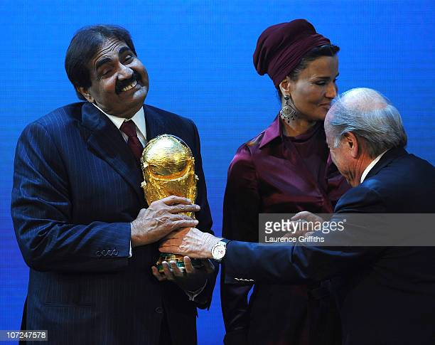 The Emir State of Qatar HH Sheikh Hamad bin Khalifa AlThani is presented with the World Cup Trophy by FIFA President Joseph S Blatter as Sheikha...