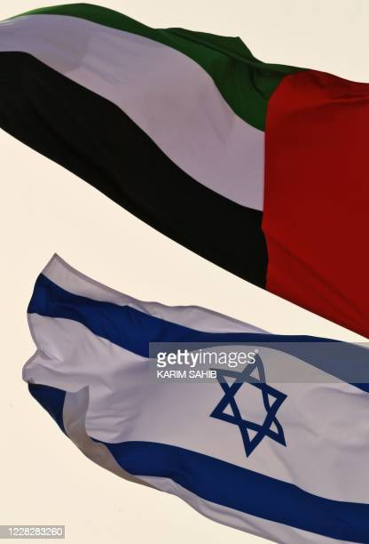 The Emirati and Israeli flags sway in the wind at the Abu Dhabi airport on August 31 after the first-ever commercial flight from Israel to the UAE. -...