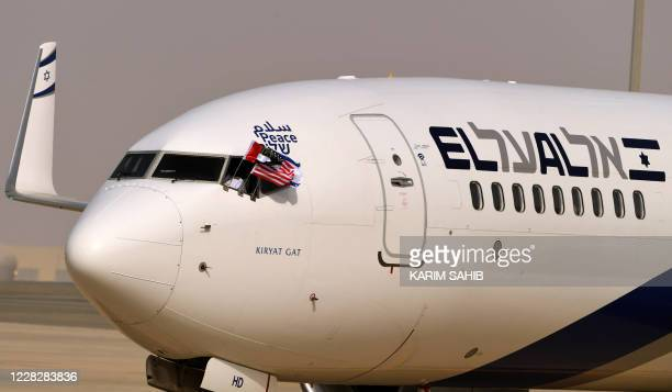 """The Emirati, Israeli and US flags are picture attached to an air-plane of Israel's El Al, adorned with the word """"peace"""" in Arabic, English and..."""