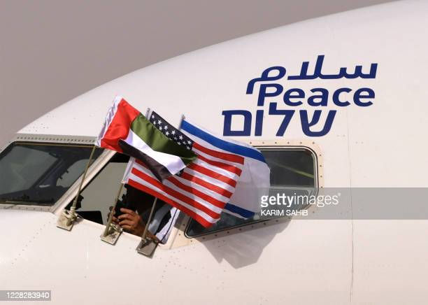 TOPSHOT The Emirati Israeli and US flags are picture attached to an airplane of Israel's El Al adorned with the word peace in Arabic English and...