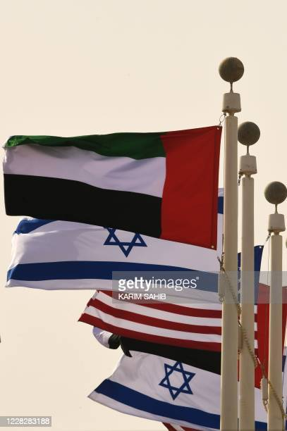 The Emirati, Israeli and US flags sway in the wind at the Abu Dhabi airport on August 31 after the first-ever commercial flight from Israel to the...