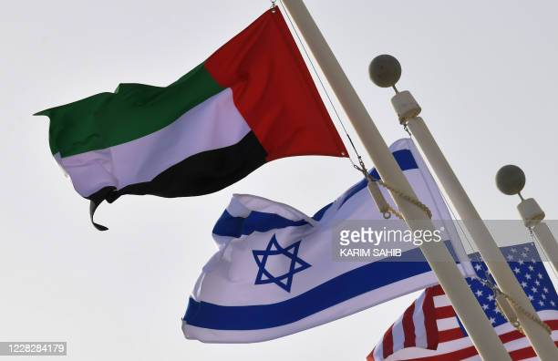 The Emirati, Israeli and US flags sway in the wind at the Abu Dhabi airport at the arrival of the first-ever commercial flight from Israel to the...