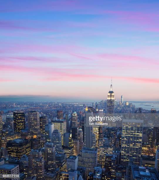 the empire state building and manhattan with illuminated buildings. - new york state - fotografias e filmes do acervo