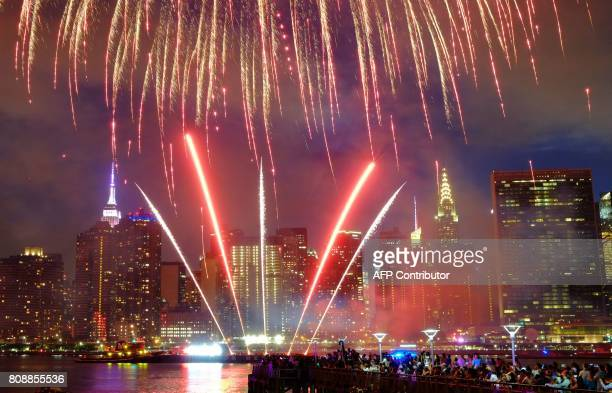 The Empire State Building and the Christal Building are seen during the Macy's 4th of July fireworks show from Queens New York on July 4 2017 / AFP...