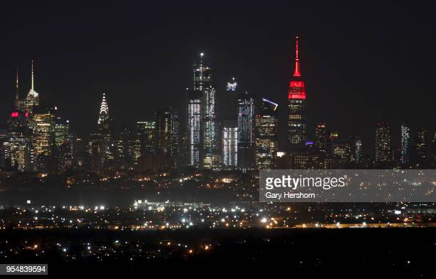 The Empire State Building glows red as night falls on the skyline of midtown Manhattan in New York City on May 2, 2018 as seen from West Orange, New...