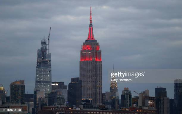 The Empire State Building in New York City is lit in red to honor NYC's Fight for Covid19 and first responders on April 4 2020 as seen from Jersey...