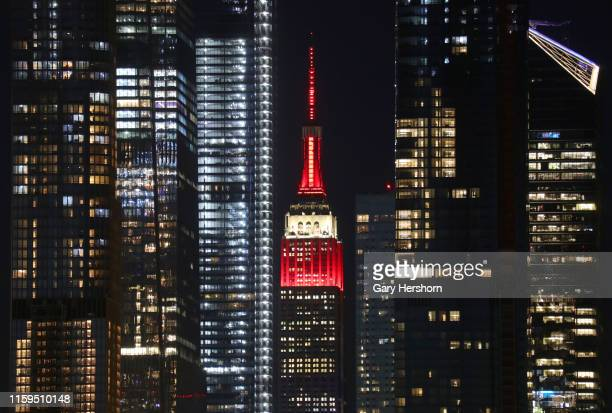 The Empire State Building is framed between the towers of Hudson Yards in New York City as it is illuminated in red and white to celebrate Canada Day...