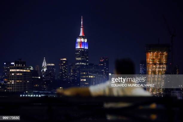 The Empire State Building is lit in honor of the 2018 World Cup Finalists France and Croatia as a man looks at the New York skyline from Hoboken in...