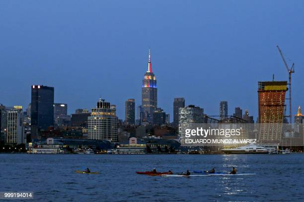 The Empire State Building is lit in honor of the 2018 World Cup Finalists France and Croatia as people kayak along the Hudson river in New Jersey on...