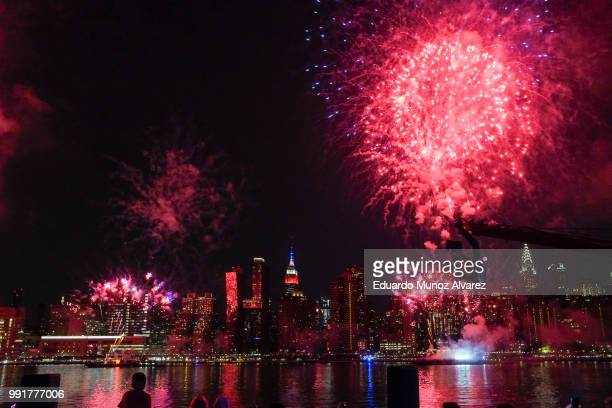 The Empire State Building is lit on blue white and red as People watch the Macy's Fourth of July Fireworks from Hunter Point Park on July 4 2018 in...