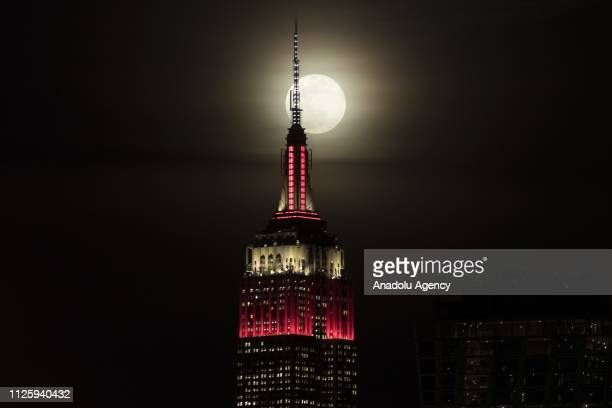 The Empire State building is seen as a super moon rises in New York United States on February 19 2019
