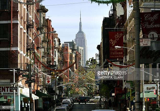 The Empire State Building is viewed from Mulberry Street in New York City's Little Italy. The steel frame, stone cladding, subdued Art Deco design...