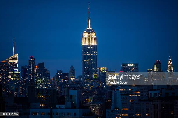 The Empire State Building still stands tall in the NYC skyline. The building is lit in white at the top this night. Chrysler Building appears on the...
