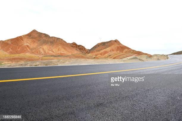 the empty asphalt road in front of danxia mountain - 甘粛張掖国家地質公園 ストックフォトと画像