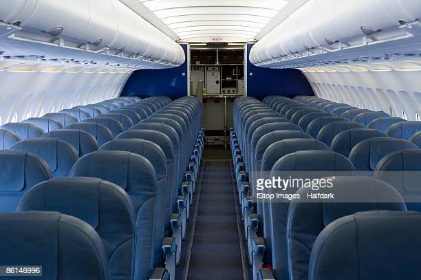 the empty cabin of an airplane - vehicle interior stock pictures, royalty-free photos & images