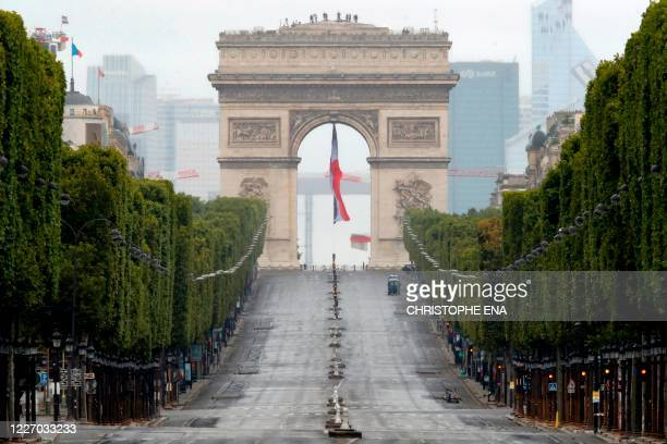 The empty ChampsElysees avenue and the Arc de Triomphe are pictured after the annual Bastille Day military ceremony held on the Place de la Concorde...