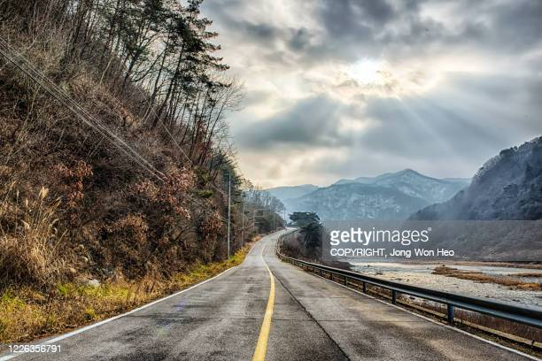 the empty road along by the river on a day with clouds in winter - gangwon province stock pictures, royalty-free photos & images