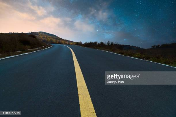 the empty road under the night sky of the milky way - paved driveway stock pictures, royalty-free photos & images