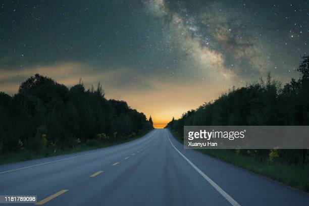 the empty road under the night sky of the milky way - long stock pictures, royalty-free photos & images