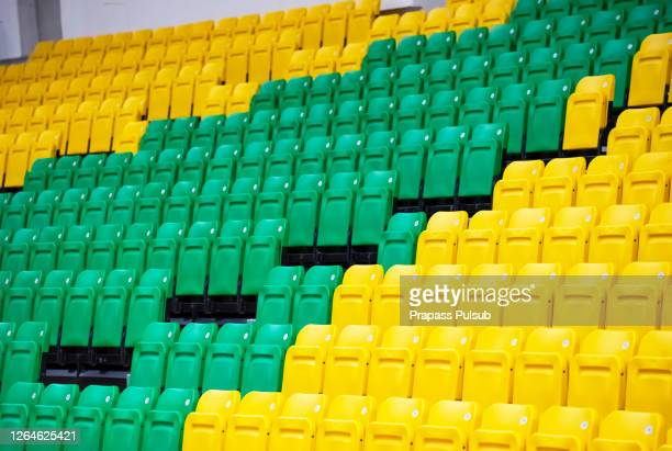 the empty seats at the stand of the outdoor sport stadium.empty colored chairs - sports venue stock pictures, royalty-free photos & images
