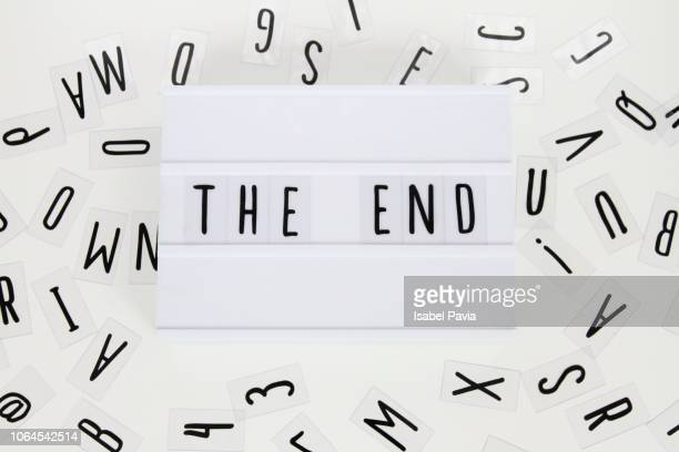 the end displayed on a light box on a white table with typography letters - lightbox stock photos and pictures