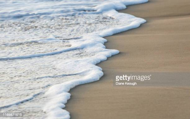 the end of an ocean wave finishing and weaving its way on the sand. - costa caratteristica costiera foto e immagini stock