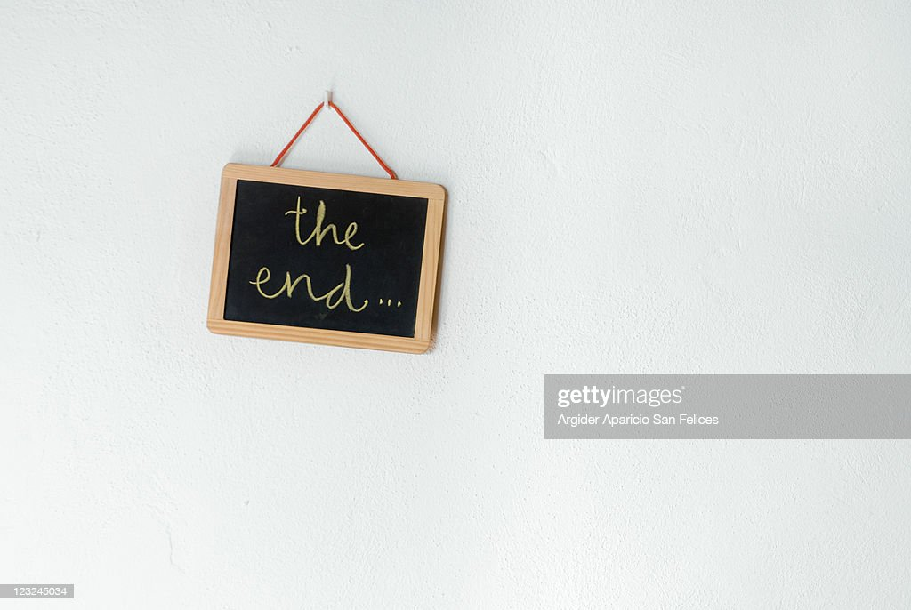 The end written on slate which is hanging on wall : Stock Photo