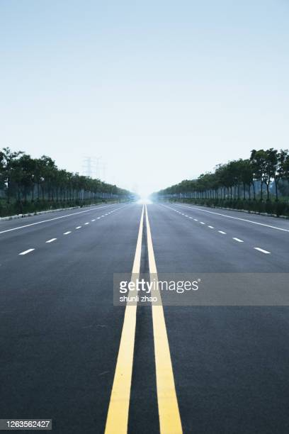 the endless asphalt road on the plain - straight stock pictures, royalty-free photos & images