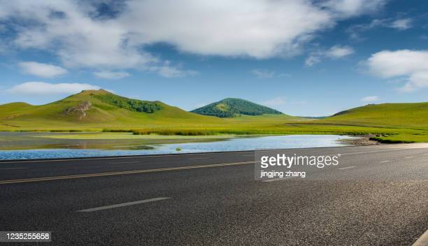 the endless grassland in spring and the forest hills in the distance beside the asphalt highway - 道 ストックフォトと画像