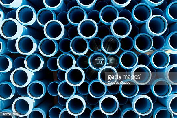 The ends of water pipes that are stacked together in a pile