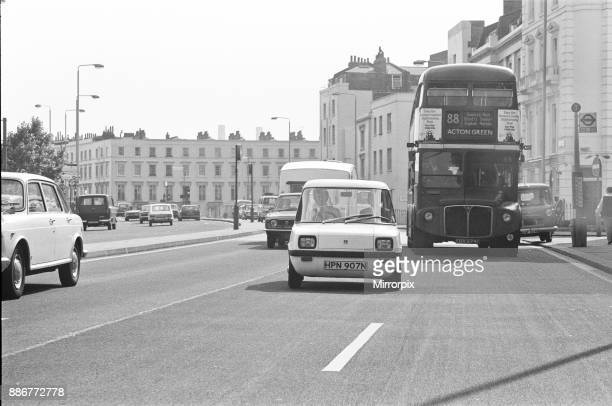 The Enfield Electric Car Road Test by Sunday Mirror reporter Roy Spicer driving The Enfield Electric car through busy London along with a London bus...