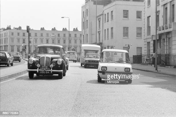 The Enfield Electric Car Road Test by Sunday Mirror reporter Roy Spicer driving The Enfield Electric car white right of pic through the busy London...