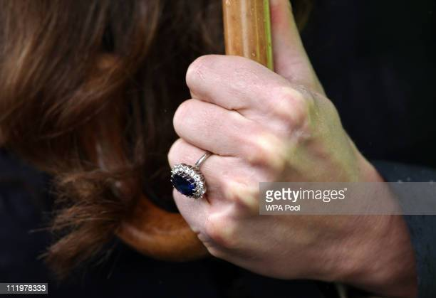 The engagement ring of Kate Middleton fiancee of Britain's Prince William is pictured as she holds an umbrella while meeting wellwishers following a...
