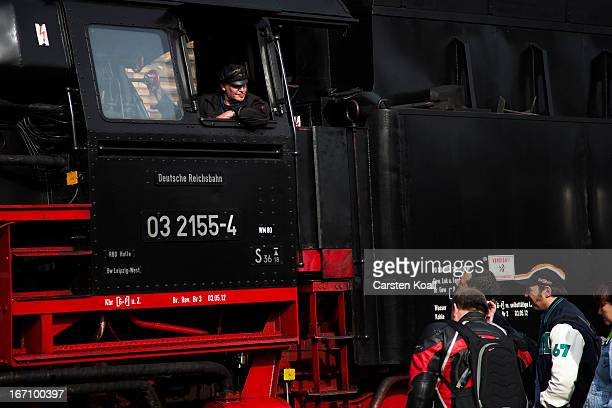 The engine driver Fiete Heilmann talks with visiors in front of the steam engine locomotive of Type 03 produced in Germany during World War II during...