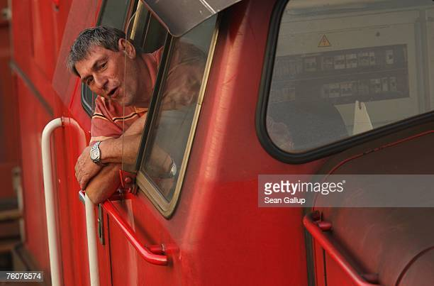The engineer of a locomotive of German rail carrier Deutsche Bahn looks out his window while pulling a cargo load at the main container port August...